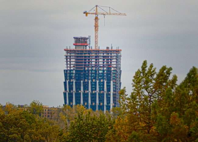 A view from Forest Park of the top of One Hundred Apartments peaking through tress shows crane and construction in Central West End neighborhood