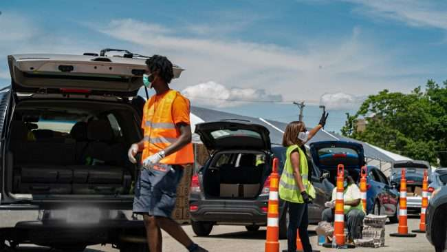 Urban League of St Louis have volunteers wear yellow and orange safety vests during Drive Through Food Pantry between 12 pm -3 pm at the Victor Roberts/ Old Sears Building in North St. Louis, May 23, 2020.