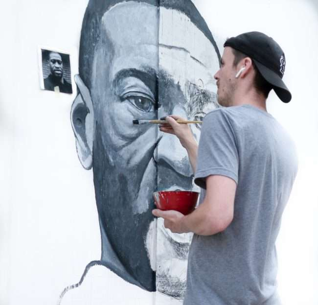 Artist Ben Angelly painting portrait of George Floyd along the Delmar Loop in University City, St. Louis. credit craig currie