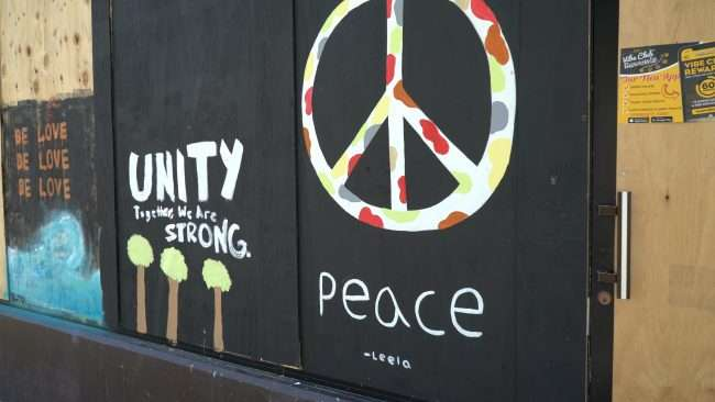 Artists Leela paints Peace Sign along The Delmar Loop in University City. credit craig currie