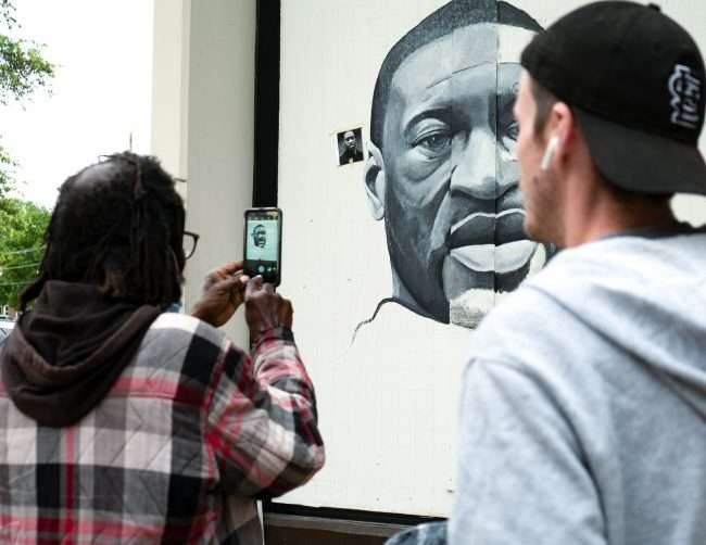 Ben Angelly and fan taking photos of painting of George Floyd along the Delmar Loop in University City credit craig currie