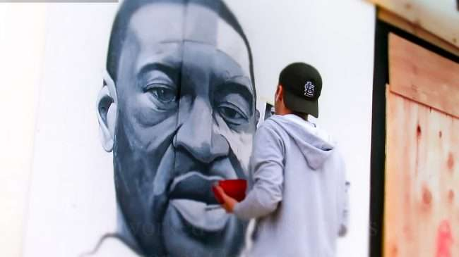 Ben Angelly paints portrait of George Floyd along the Delmar Loop in University City.
