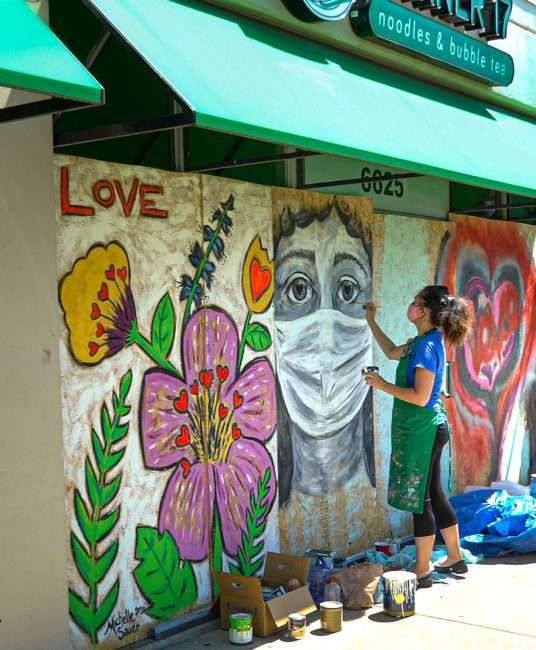 Artist Michelle Sauer paints woman in mask by Corner 17 Noodle eatery along Delmar Loop in University City. credit craig currie