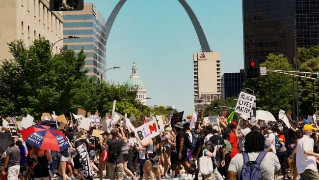 Protester on Market and Tucker with Arch and Old Courthouse in back ground in Downtown St. Louis, MO.