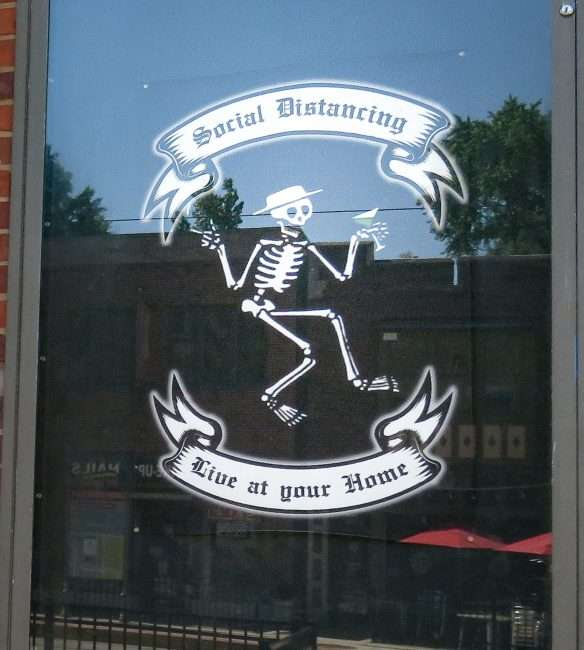 "Poster that reads ""Social Distancing"" with animated skeleton taped on Pageant door in The Delmar Loop. (credit craig currie June 1, 2020)"