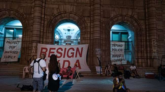 Occupy St. Louis City Hall hangs sign Invest In Community. credit craig currie