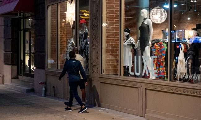 A couple window shops at LUXE Women's Wear and clothing store on Washington Avenue in Downtown St. Louis. (August 28, 2020)
