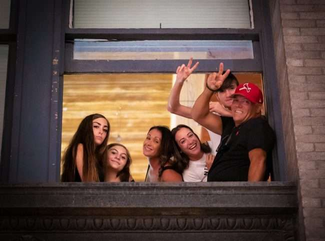 Family waves from window on the barricaded section of Washington Avenue in Downtown St. Louis.(August 28, 2020)