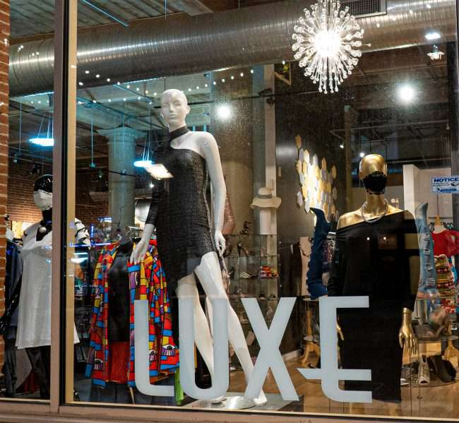A lighted window with fashion designs at the LUXE Affordable Luxury Clothing Store on Washington Avenue while street is blocked off from traffic due to late-night racing in Downtown St. Louis. (Aug 28, 2020)