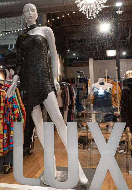 A lighted decorated window with mannequin in dress at the LUXE Affordable Luxury Clothing Store on Washington Avenue while street is blocked off from traffic due to late-night racing in Downtown St. Louis. (Aug 28, 2020)