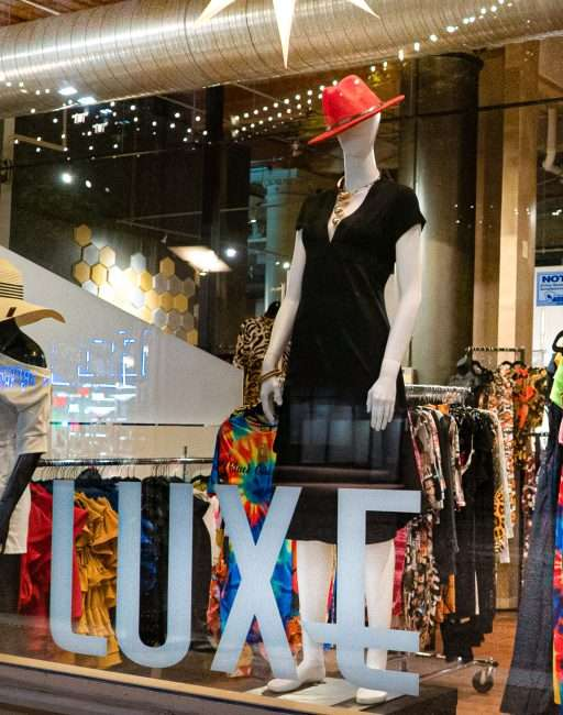A lighted decorated window with mannequin in dress and red hat at the LUXE Affordable Luxury Clothing Store on Washington Avenue while street is barricaded from traffic due to late-night racing in Downtown St. Louis. (Aug 28, 2020)