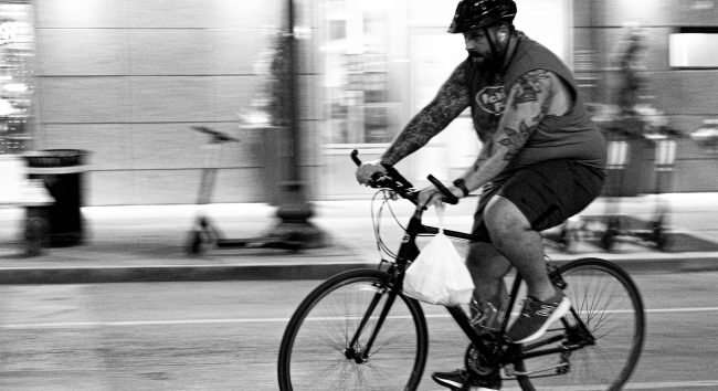 Man riding bike on Washington Avenue while the street is barricaded due to late-night racing in Downtown St. Louis. (Aug 28, 2020)