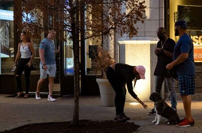Neighbors gather while petting dog on sidewalk on Washington Avenue during the street being barricaded due to late night racing in Downtown St. Louis. (Aug 28, 2020)