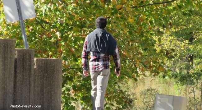 Gentleman walking on sidewalk Forever Forest Park. credit craig currie