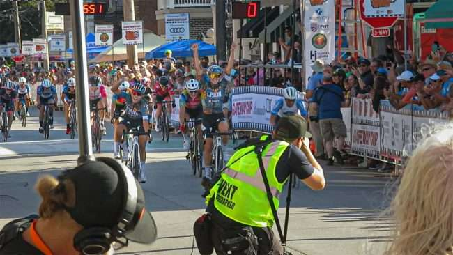 Gateway Cup Women's Pro bike race winner with hands up in Hill neighborhood in St. Louis. credit craig currie